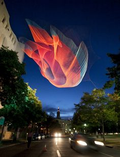 Janet Echelman's sculptures are woven — much like fishing net — and their light, mesh material allows them to move fluidly in the sky, morphing and billowing in the wind like some sort of strange, beautiful, grandma-knitted Northern Lights.