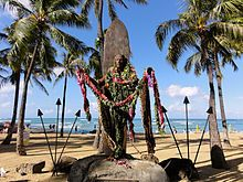 A monument at Waikiki beach in Honolulu honors his memory. It shows Kahanamoku standing in front of his surfboard with his arms outstretched. Many honor him by placing leis on his statue. There is a webcam watching the statue, allowing visitors from around the world to wave to their friends.