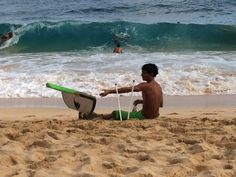 Tossing a wrecked body-board aside next to the dangerous surf of Sandy Beach
