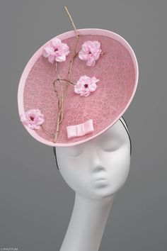 Anastasia is a couture saucer-like shaped fascinator highlighted by an impregnated tree root completed with four flowers and a little bow. This headwear is hand formed and sewed, making it an exclusive design. Most certainly this artisan fascinator will grasp affirmative attention when worn at the races or to a wedding.
