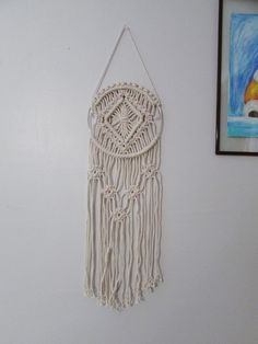 This beautiful macrame wall hanging will add the perfect touch of modern macramé to any room in your home. It is handmade with natural cotton rope. SPECIFICATIONS: 19 long 6 ring Hangs from a 4 1/2 string (total length: 23 1/2) Follow me on Instagram @ModernKnotDesigns and Facebook.com/ModernKnotDesigns Please reach out to me if you have any questions or concerns.