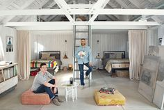 Henry and Oliver (holding Atticus the bunny) kick back in the barn, which serves as both their art studio and sleeping quarters. Henry painted the oil work at left; Oliver's canvases are stacked on the other side of the room. Corbin constructed the ladder leading to the loft, and the steel bed frames are Room & Board bargains. Bright idea: Curtains sewn from drop cloths provide privacy for each nook.