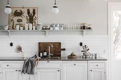 Luckornas utformning, den vita basen och kakelsättningen är sekelskifte 1900. Gediget och med traditionens trygga estetik mitt i vår tids köksvardag.