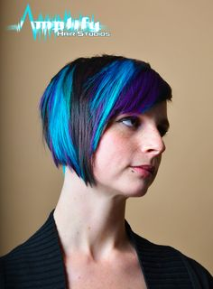 A asymmetrical hairstyle with funky, dramatic haircolor. This haircut is shaved on the left side through the back and the top and right side are disconnected. The cut is complimented with a beautiful contrast of black, purple and turquoise.