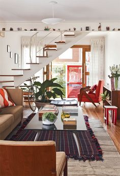 I love the use of that narrow space above the stairwell for display and the open concept of the floor plan.
