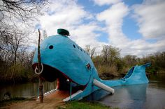 the big blue whale in catoosa, oklahoma...we swam here as kids. there was a big wooden ark, tiki hut bathrooms/change houses, colorful cement ice cream tables, dive platforms and docks. closed in 1988, now an official Roadside America Route 66 attraction.