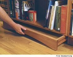 Hidden drawer under bookcase.
