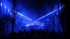 """""""Axial"""" is an audiovisual immersive space. Through the digital manipulation of 16 motorized light beams, dynamic light architectures are created, which evolve in space and time, creating alive forms"""