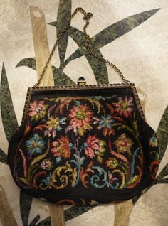 Gorgeous needlepoint bag from 1920s, with an enamelled pattern on the front of the frame to match the clasp. To open the bag, the clasp slides left and lifts, and to close this is reversed and the clasp pushed right and back to the centre. The outside of the bag, the frame and clasp are all in excellent condition. The lining inside is mostly good, but there is some splitting in the silk near the frame. Measurements:  Length of bag: 5.75   Width: 7 at widest point, frame 5.25  Depth: 1…