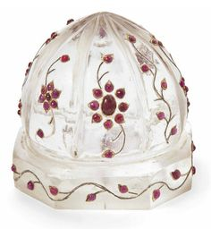 A GEM-SET ROCK CRISTAL CARPET WEIGHT MUGHAL INDIA, 18TH/19TH CENTURY In the form of a ribbed dome on an octagonal base, the gem-set decoration with foiled rubies in floral patterns and simple scrolling vine, numerous gemstones are later replacements