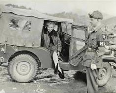 Marilyn Monroe posing in a jeep, as an unknown MP stands nearby - Korea 1954