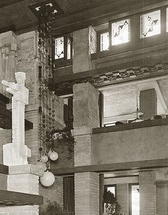 Detail of Southwest corner of the Winter Garden. Male Sprite holding cubes sits atop a pedestal, attached to the front of the balcony; patterned ceiling; sculptured capital; hanging light fixture, and row of leaded glass windows.
