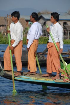 A group of locals row on a 50-men boat as part of a ceremony to accept new monks to the local monastery in Inle Lake, Myanmar