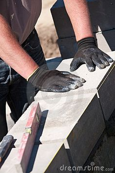Glove hands of builder laying wall with spirit level in foreground.