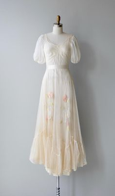Achingly lovely 1930s cream silk net lace dress full length and sheer with unattached silk slip, scoop neckline, puff shoulder sleeves, seamed waist, tiered ruffle hem and pastel crewel flowers around the skirt. Shown with simple cream ribbon belt, not included. --- M E A S U R E M E N T S ---  fits like: xs bust: 32-33 waist: 24-26 hip: free length: 51 brand/maker: n/a condition: amazing condition considering its delicate, airy construction - there is some tiny holes at the hem and...