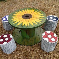 table basse touret, décorée d un dessin de tourne sol et petits buches décorés en guise de tabourets pour aménager un coin de jeux a l exterieur