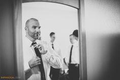 Groom tying Tie with groomsmen behind, toronto wedding photographer raph nogal, cambridge mill