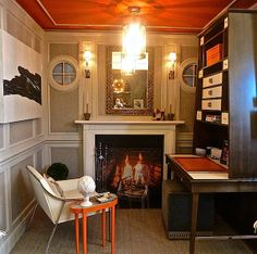 """Saranda Berisa's elegant space for """"Rooms with a View"""" vignettes. Handsome bespoke millwork and a beautiful Chesney's fireplace set the tone for a timeless tailored sitting room.Grounded by a putty Farrow and Ball paint with herringbone Phillip Jeffries wall covering, a bright orange ceiling and accents brought the room to life. An Oomph Tini II Z Table and accessories from local favorites Pimlico and The Summer House imbued the space with a youthful tone."""