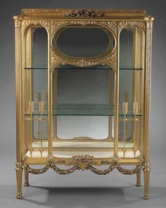 An Antique Louis XVI-Style Carved and Giltwood Vitrine Cabinet, late 19th c., the cushion molded top with husk moldings centered by a cluster of blossoms, turreted sides, paneled front with arched and oval glazing with arrow motif, swagged skirt, the doors opening to the sides, ending in fluted legs with disc feet, height 60 in., width 43 in., depth 15 in.