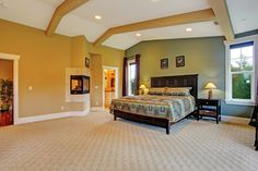 The bright, Aztec-style print of the bedding is the focal point of this spacious, if oddly shaped, room. The fireplace juts out of the wall and is open to two sides of the room.