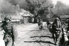 German soldiers moving through a Russian village, leaving burning houses behind..