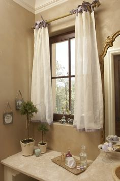French Provencal bathroom, ribbon is used as a border at the hem, and to tie the billowy curtains to the fluted rods.