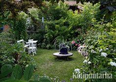 Pieni istuskeluryhmä kutsuu nauttimaan puutarhan väreistä, tuoskuista ja rehevästä tunnelmasta.