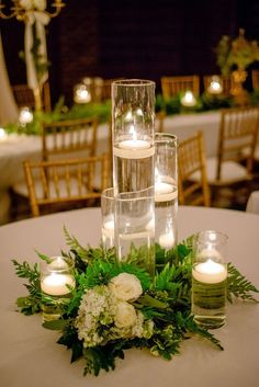 The reception tables were decorated with white table lines, floating candles inside cylinder hurricane vases and lush florals. Venue / Coordinator: East Ivy Mansion