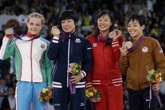 From left, silver medalist Mariya Stadnyk of Azerbaijan, gold medalist Hitomi Obara of Japan, bronze medalist Carol Huynh of Canada, and bronze medalist Clarissa Kyoko Mei Ling Chun of the United States, participate in the awards ceremony for 48-kg women's freestyle wrestling at the 2012 Summer Olympics, Wednesday, Aug. 8, 2012, in London.