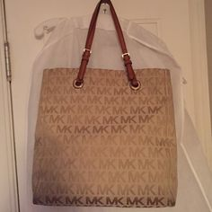 Micheal Kors tote Signature MK fabric tote with brown leather handles. Very roomy inside. 14 x 14. Outside bottom of the purse has a little wear but no spots, holes or stains on the outside. Michael Kors Bags Totes