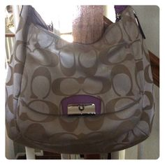 Coach WILLING TO TRADE! Beautiful Coach bag. It's large has purple leather straps and a nice size pocket on the front with the Coach logo on the silver latch! Used a few time a little ink inside of the purse. One lg zipper pock and 2 small pockets on other side! Coach Bags Hobos