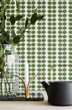 A bold linear print wallpaper design featuring bright green leaves on a cream background.