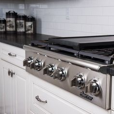 American-made and family-owned company Dacor provided innovative kitchen appliances, including a range top stove, cabinet deck refrigerator with French doors, and wall oven. (NOTICE the six burners including grill or warming plate?)