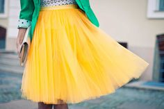bright yellow tulle skirt, black and white polka dot shirt, and green cuffed blazer with a big clutch