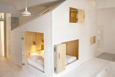 L'architetto e designer Sigurd Larsen ha progettato una camera d'albergo a Berlino, con un volume bianco e puro le cui numerose aperture rivelano un caldo interno di legno.