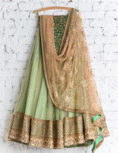 Shop designer net with famed embroidery lehenga choli online.This set is features a green blouse in silk embroidery and sequins work.It has matching beige lehenga in net with beautiful embroidery all over and brown dupatta in net. We ship worldwide to Yem Indian Suits, Indian Attire, Indian Dresses, Indian Wear, Indian Style, Pakistani Dresses, Indian Ethnic, Green Lehenga, Indian Lehenga