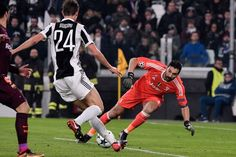 Juventus' goalkeeper from Italy Gianluigi Buffon (R) makes a save during the UEFA Champions League Group D football match Juventus Barcelona on November 22, 2017 at the Juventus stadium in Turin. .Barcelona advanced to the Champions League last 16 on Wednesday after clinching top spot in Group D following a 0-0 draw against Juventus in Turin. / AFP PHOTO / Federico TARDITO