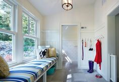 Large white mudroom clad in shiplap lower wall trim is equipped with a white long built-in bench fixed beneath a window and topped with a blue striped seat cushion accented with yellow and gray pillows.
