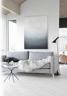 Light grey sofa paired with a beautiful faux fur throw. Surrounded by black metal acessories and light colour furniture. Minimal design.