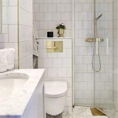 Guldglans. Badrummet är en mässingdröm med produkter från Vola och Tapwell. Färganpassade handdukstorkar från INR.