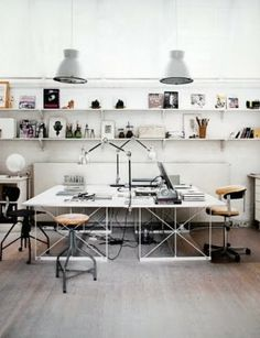 I love the huge worksurfaces, funky chairs, and museum-like display of this setup!