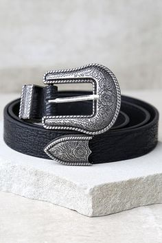 """Take a walk on the wild side and create a fierce look with the Wandering Wilderness Silver and Black Belt! A silver belt buckle with engraved detail embellishes this vegan leather belt. Belt measures 40"""" long with seven hole adjustments."""
