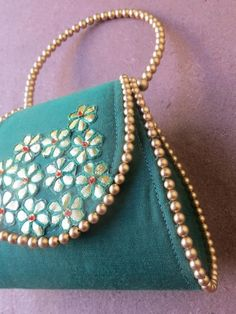 Green clutch bag features hand embroidered gotta flowers detail and gold beaded handle with rich green color .  Shop for this Green gotta flower clutch bag. Beaded handle and trendy shape make this bag more wanted.