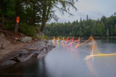 To get each shot, Orlando attaches Technicolor LED lights to the paddles of the vessels. He then takes long exposure photographs of the rowers in motion, capturing the light's path, revealing the paddle's pattern