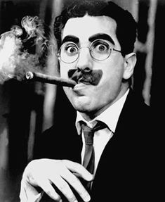 """Groucho Marx (American comedian film television radio star) known for his quick wit and considered one of the twentieth century's best comedy star. He is most noted for his radio then turned television game show, """"You Bet Your Life."""" His signature look with heavy black grease make up and mustache large frame glasses and big nose."""
