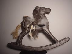 Paper mache rocking horse with leather and pheasant feathers