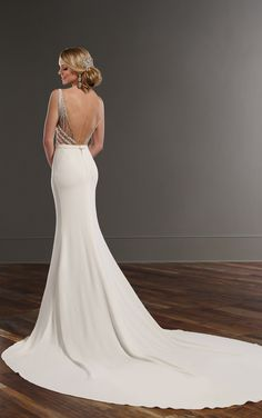 This modern wedding gown from Martina Liana features a beaded illusion bodice with graphic lines and keyhole details. The smooth Bellagio crepe skirt falls elegantly into a cathedral train. The low-cut back zips up under fabric-covered buttons. Detachable Bellagio crepe belt included.