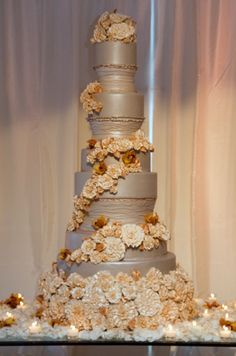 Peach and gold sugar flowers accent a fondant-covered cake  with carved, textured layers.