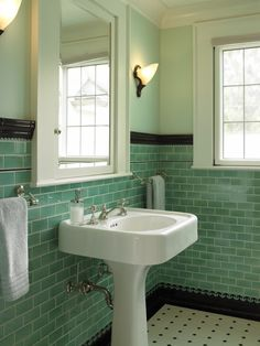 Classic vintage style can transform a bathroom into a little jewel box. The height of this tile, coupled with the natural light, reflects and shines; the black and white tile accents give it fun apothecary appeal.