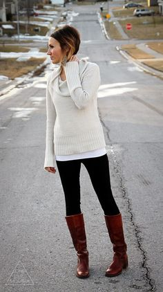 Long sweater paired with black knit pants and tall brown boots